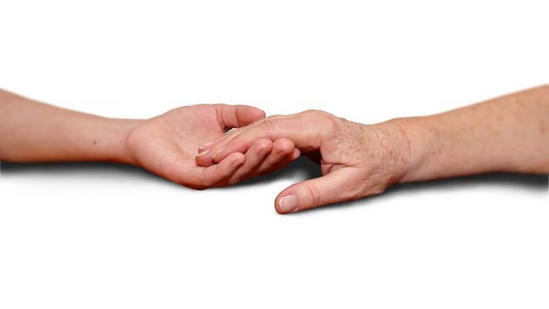Die Hand einer Patientin wird unterstützend gehalten von einer anderen Hand.