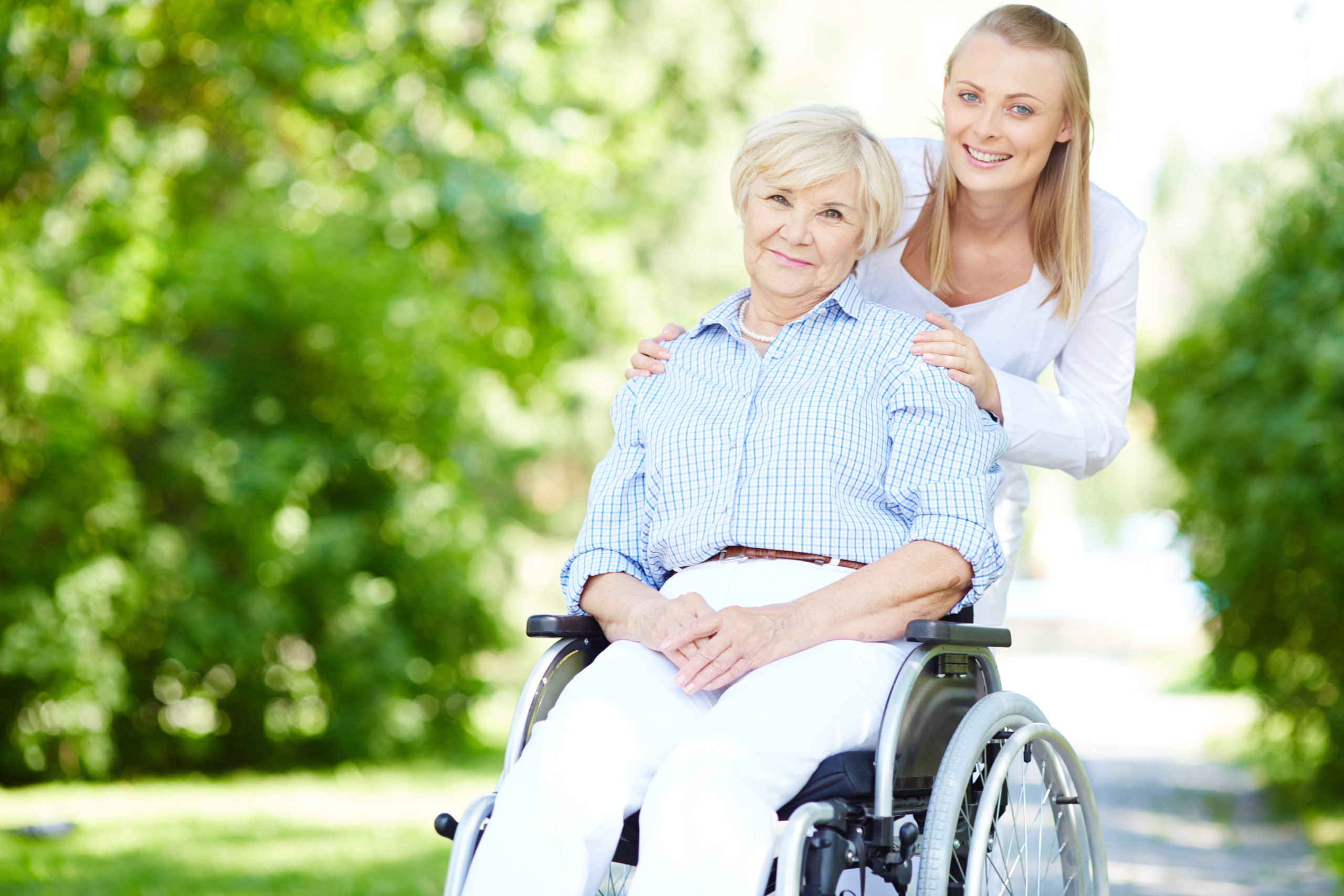 Eine Rentnerin im Rollstuhl und ihre Pflegerin machen einen Spaziergang im Park