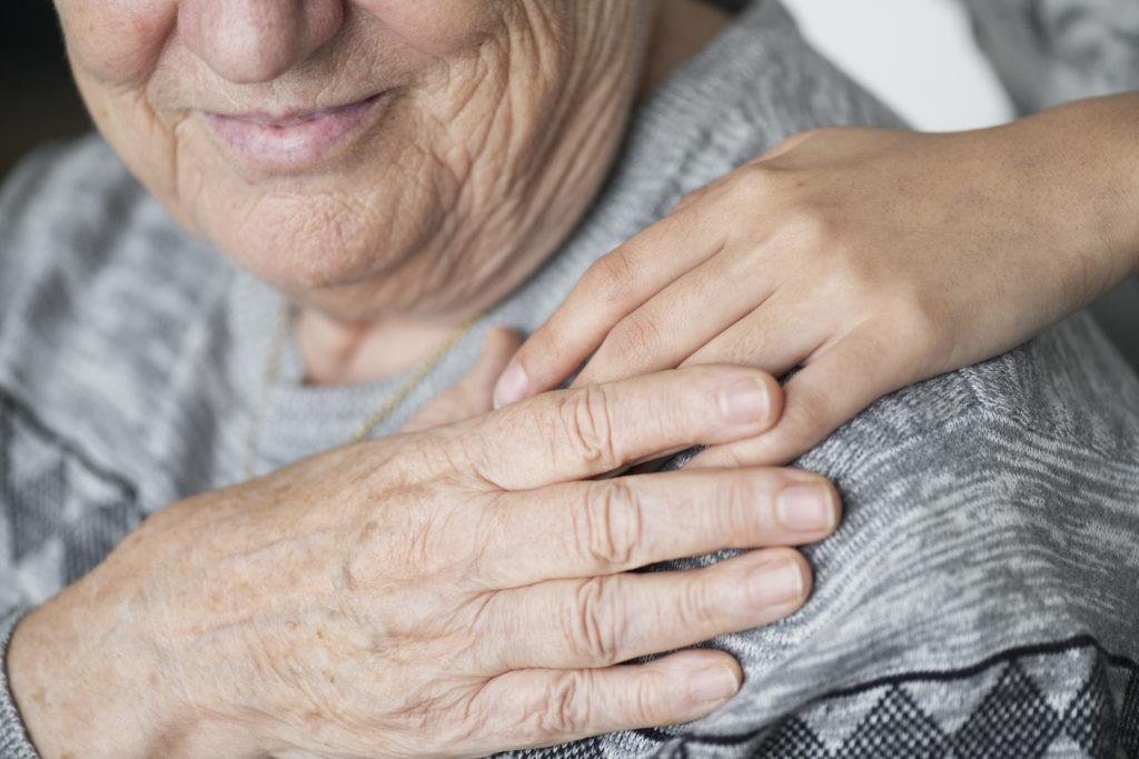 Als ermutigende Geste legt eine Pflegerin eine Hand auf die Schulter einer Patientin. Die Patientin freut sich darüber.